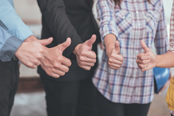 a group of people point thumb together