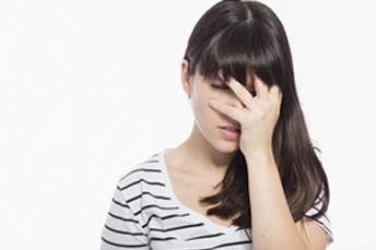a girl is frustrated by covering her face