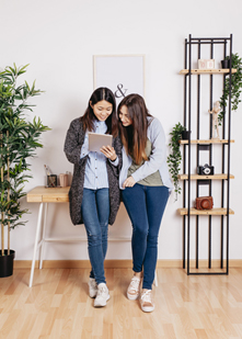 2 standing girls looking at a tablet